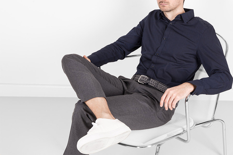 Model sitting on a chair wearing his blue and grey braided belt.