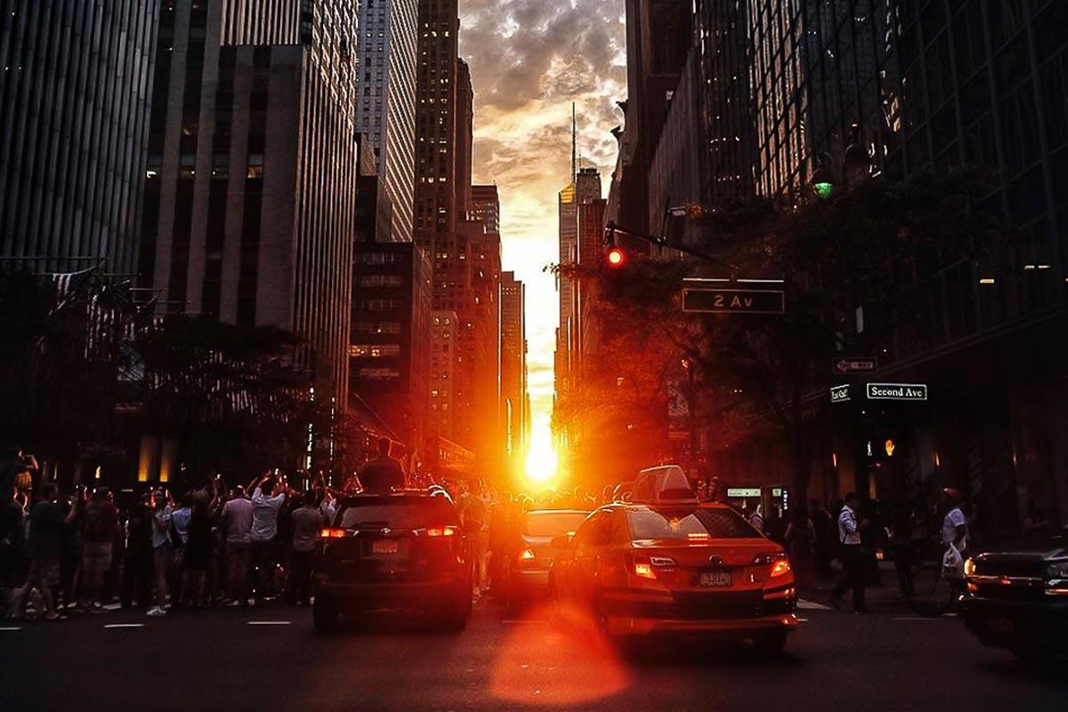 Zuschauer auf New Yorks 42nd Street beobachten des Manhattenhenge Spektakel.