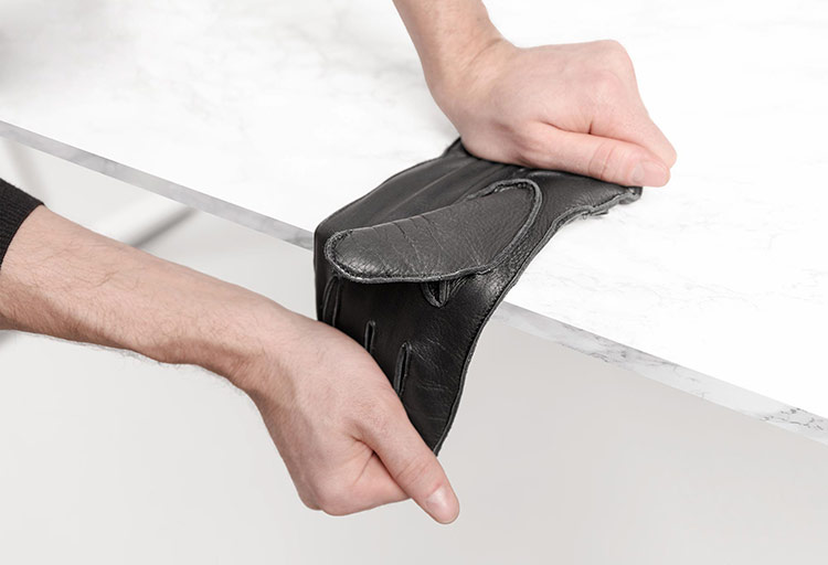 Schwarzer Hirschleder Handschuh wird über Tischkante gezogen